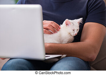 Man working on laptop and playing cat