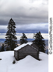 Old wooden hut in winter snow mountains and gray sky with...