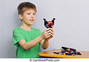 Boy with a toy of plastic parts
