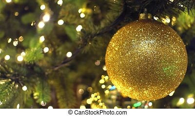 Decorated Christmas tree. Golden ball 4K close-up shot -...