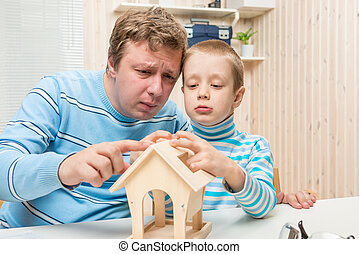 concentrated father and son building a bird feeder in the...