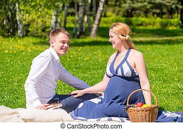 man and his pregnant wife on picnic in the park
