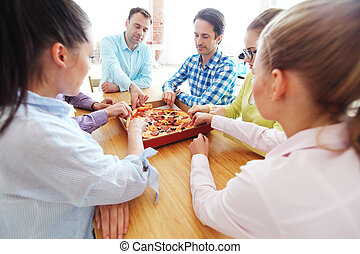 Friends taking slices of pizza