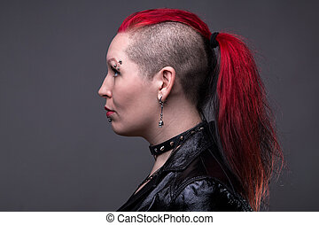 Rock woman with shaved head on gray background
