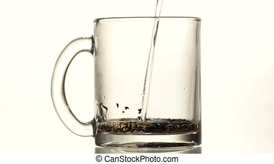 The cup of tea is poured boiling water - A glass cup of...