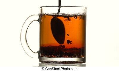 Black tea is stirred with a spoon - Black leaf tea with...