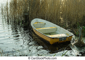 Small boat in a lake in the fall