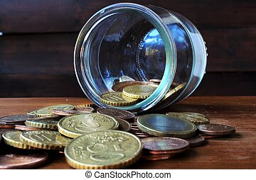 money - coins faling from glass bottle on the wood table
