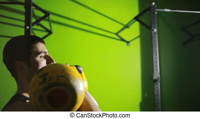 Young athletic man doing kettlebell swing exercise at the...