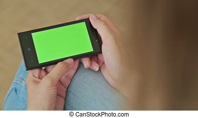 Pretty woman holding smart phone with green screen display...