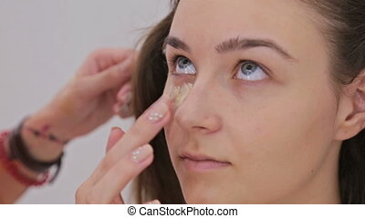 2 shots. Professional make-up artist applying cream base eyeshadow primer to model eye