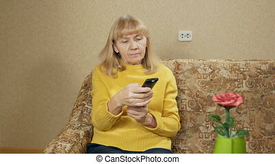 Woman aged switches remote control TV channels on the couch at home. She is resting after a hard day. holiday concept