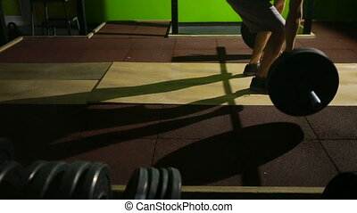 Young man doing deadlift exercise at gym. barbell