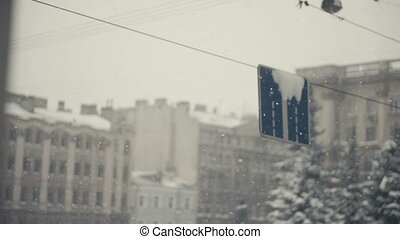 Road signs In Snowfall slow motion. Cityscape defocused on...