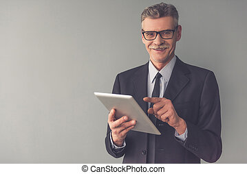 Handsome mature businessman in formal clothes and eyeglasses...