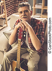 Handsome mature man with guitar - Handsome mature man in...