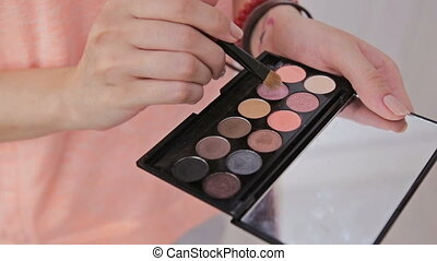 Make-up artist taking eye shadows from makeup eyeshadows...