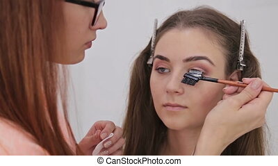 Professional make-up artist combing eyelashes of model in...