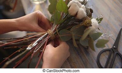 Florist girl hands closeup making a flower composition
