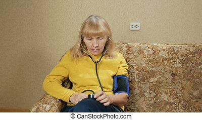 Woman aged measures the pressure of their own home on the...