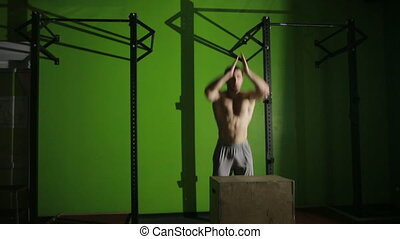 muscular man doing a box jump. gym. CrossFit - man doing a...