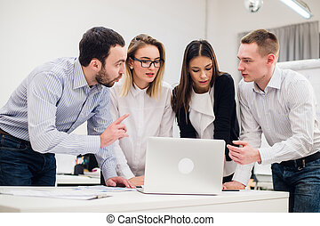 Colleagues at an office meeting talking and working on a laptop