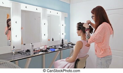 Hairdresser finishing hairstyle for young pretty woman - Top...