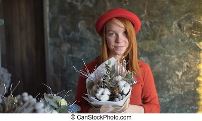 Florist girl smile and shows a flower composition