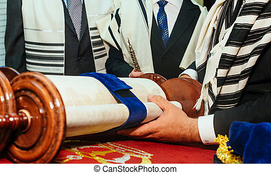 Hand of boy reading the Jewish Torah at Bar Mitzvah -...