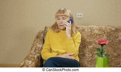Woman aged talking on a mobile phone on the couch at home. moving the camera