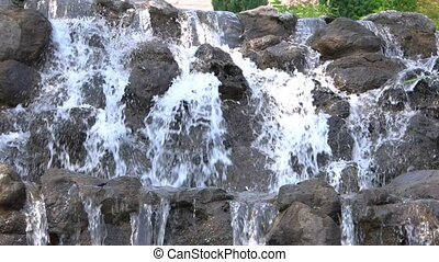 Small waterfall in motion. Water flowing on rocks. Feel the...