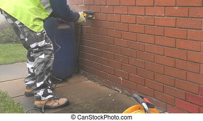 Raking out old mortar using grinder - Construction worker is...
