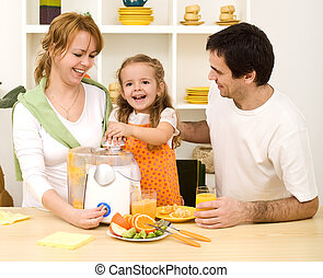 Making fresh fruit juice - Happy family with a kid making...