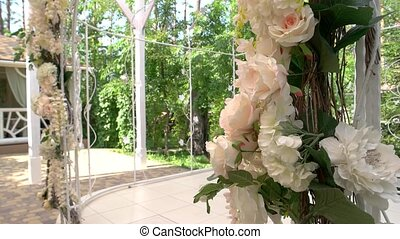 Wedding arch with flowers. Light-colored roses and leaves....