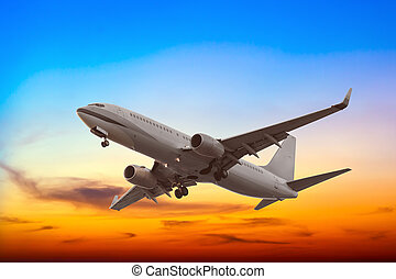 Commercial airplane flying with beautiful sunset background