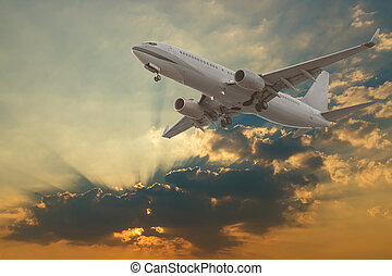 Commercial airplane flying with clouds and sun rays...