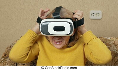 Senior woman wears glasses of virtual reality and watching a movie. She looks around and wants to touch the virtual walls. holiday home concept