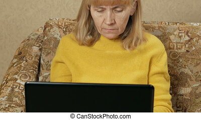 Woman aged carefully works at a laptop at home on the couch. She is typing on keyboard and looking at the screen. The concept of working at home