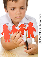 Sad kid cutting his paper people family - divorce concept,...