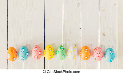 Colorful easter eggs on rustic wooden white background with...