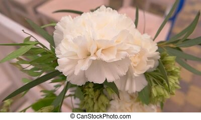 Flowers and green leaves. Carnation of white color. Sense...