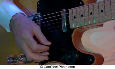 Male hands playing electric guitar. Man with a musical...
