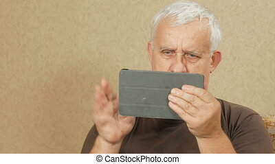 The man at the age of the tablet communicates with relatives...