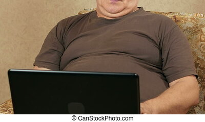 The man at the age of home working at a laptop on the couch. He is typing with both hands and carefully checks written. home working concept