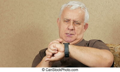 Senior man come messages on smart watches at home on the...