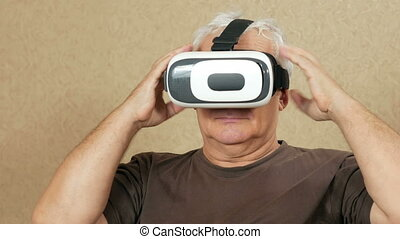 The man wears glasses at the age of virtual reality at home on the couch. He wags his head and wants to touch the hands of what is happening. Future technology concept