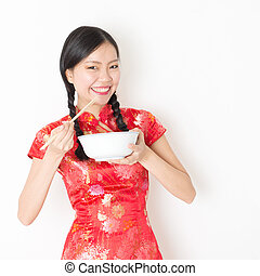 Oriental woman in red cheongsam eating with chopsticks -...