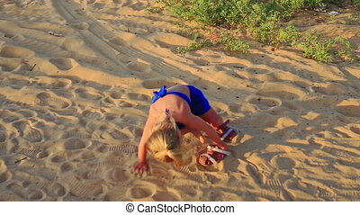Small Girl Stops Takes off Sandals on Sand Dunes at Sunset -...