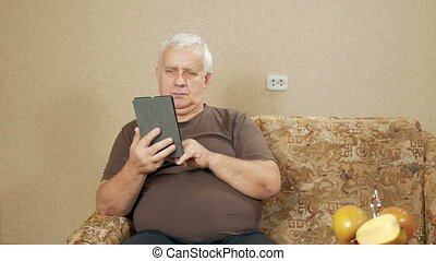 The man at the age of the tablet reads the news at home on the couch. He leafs through the finger is not interesting pages. holiday home concept