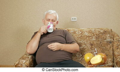 The man at the age of drinking coffee from a cup and looking at the camera. He relaxes at home on the couch after a hard day. holiday home concept